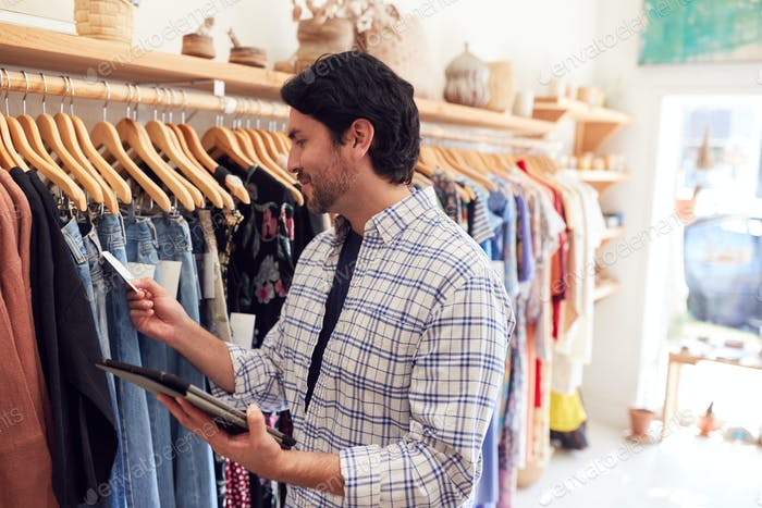 Male Owner Of Fashion Store Using Digital Tablet To Check Stock On Rails In Clothing Store