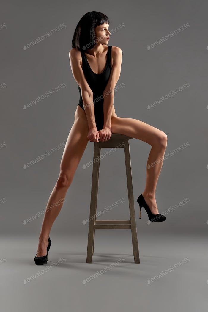 Сексуальная модель позирует, сидя на стульчик