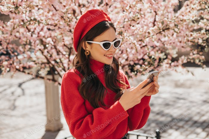 Attractive lady in stylish spring outfit with smile looks into phone against backdrop of blossoming