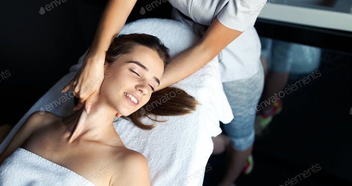 Masseur doing massage on female body in the spa salon. Beauty treatment concept