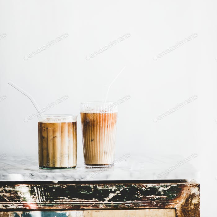 Iced latte coffee in glasses, whate wall background, square crop