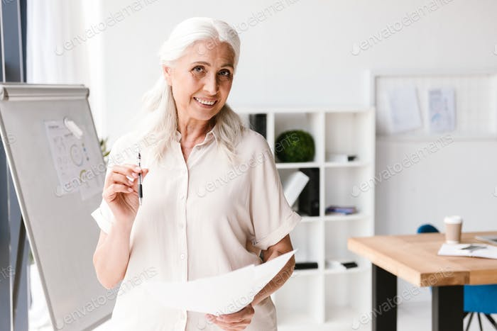 Smiling mature business woman analyzing documents