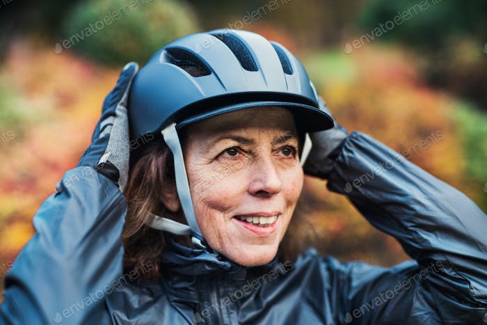 A close-up of active senior woman standing outdoors, putting on bicycle helmet.