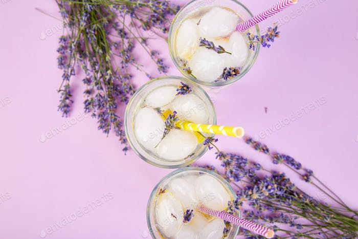 Lavender lemonade with lemon and ice on purple background.