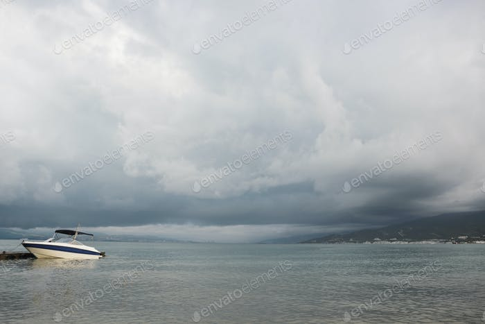 small sport fishing white boat on approaching storm background