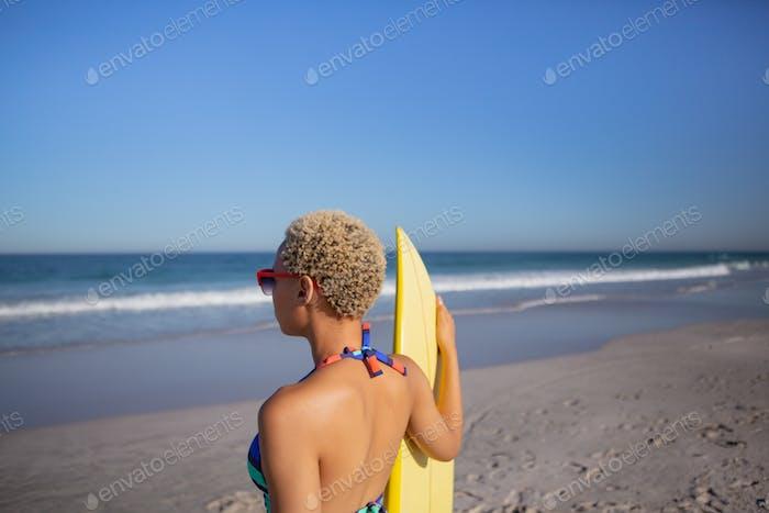 African American Frau im Bikini und Sonnenbrille stehend mit Surfbrett am Strand in der Sonne
