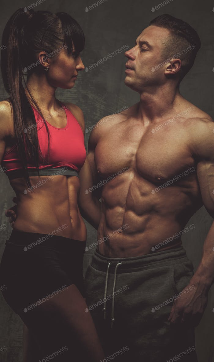 Woman and man bodybuilders posing in studio