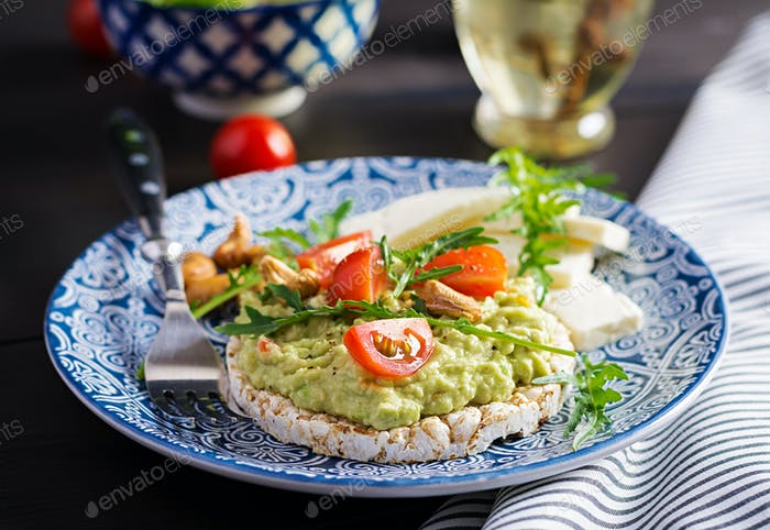 Healthy avocado toasts for breakfast or lunch,  guacamole avocado, kalamata olives, tomatoes