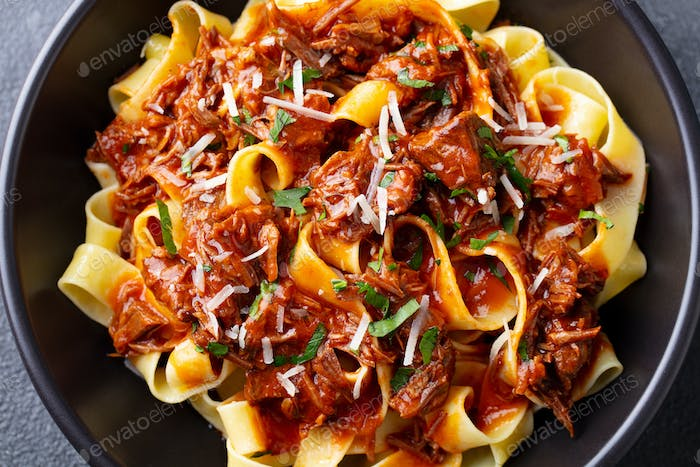 Pasta Pappardelle with Beef Ragout Sauce in Black Bowl. Close up.