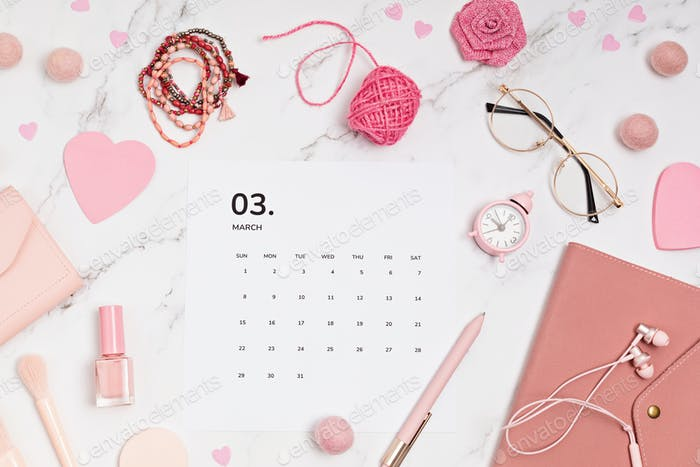 Desktop with calendar for march and pink accessories. home office, social media blog idea
