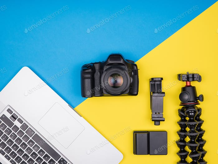 Camera with accessories next to a laptop