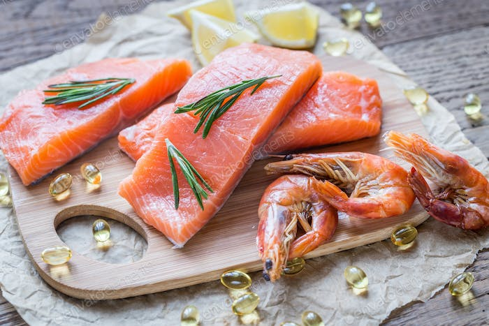 Raw salmon with shrimps on the wooden board
