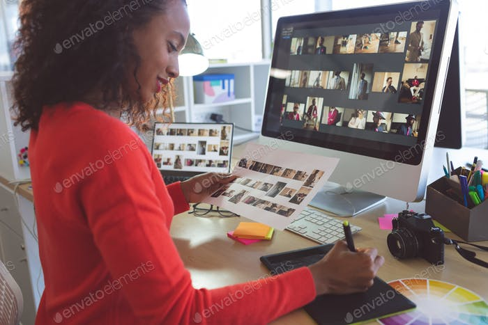 Female graphic designer writing on tablet in a modern office