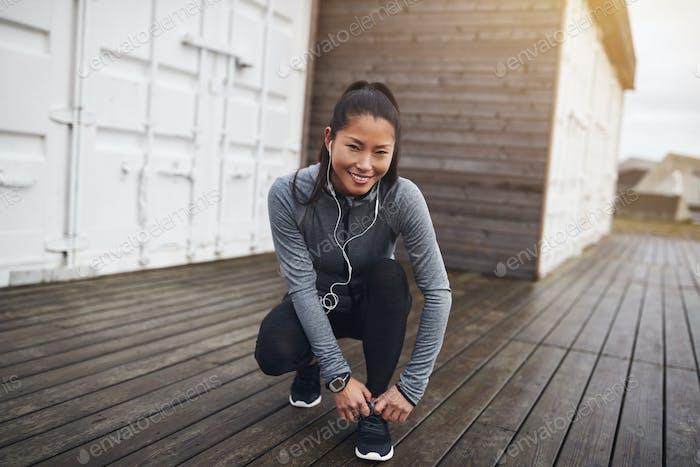 Young Asian woman tying her running shoes before a run