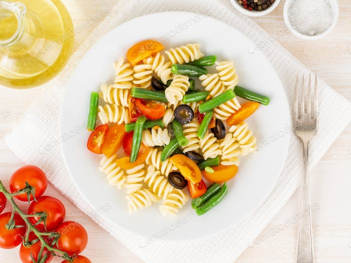 Italian salad with fusilli paste tomatoes, olives, green beans, top view, close up