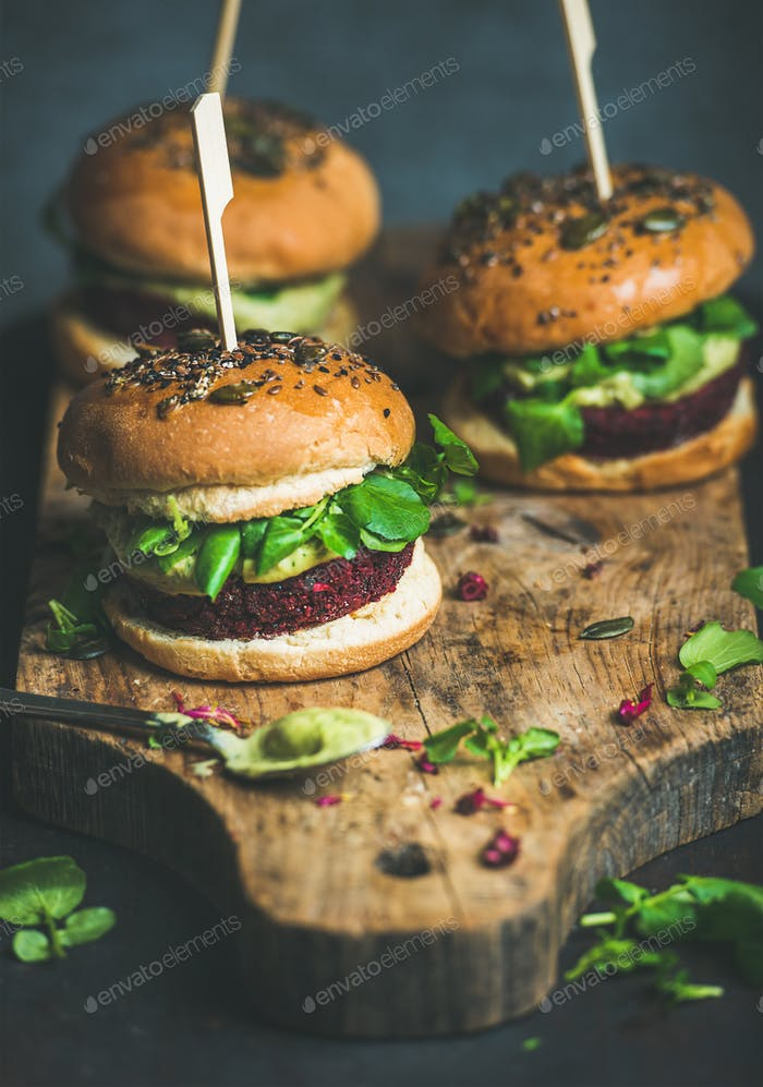 Healthy vegan burger with beetroot-quinoa patty, arugula on board
