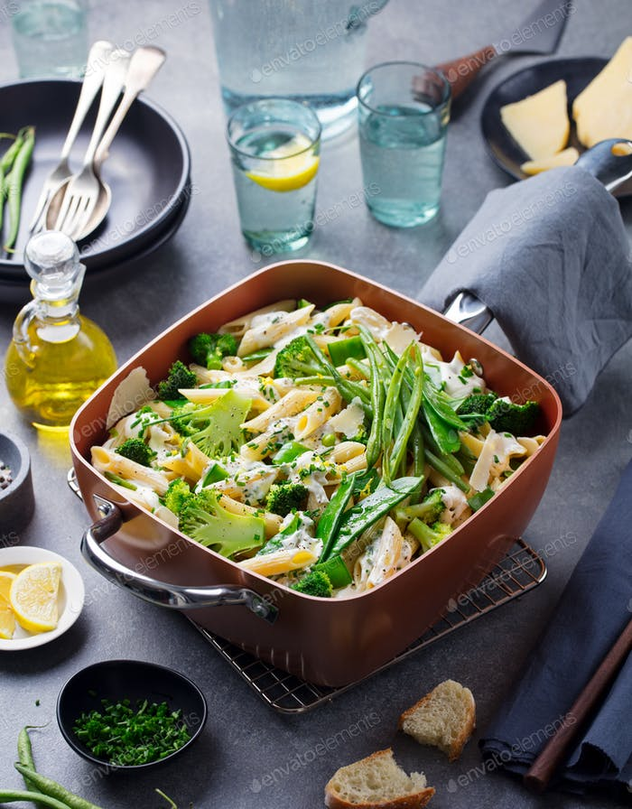 Pasta with Green Vegetables and Creamy Sauce in Copper Saucepan. Grey Stone Background.