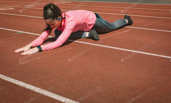 Woman performing stretching exercise on a race track