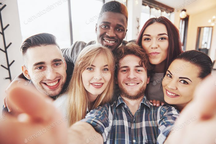 Two boys and four girls drinking making selfie, making peace sign and laughing