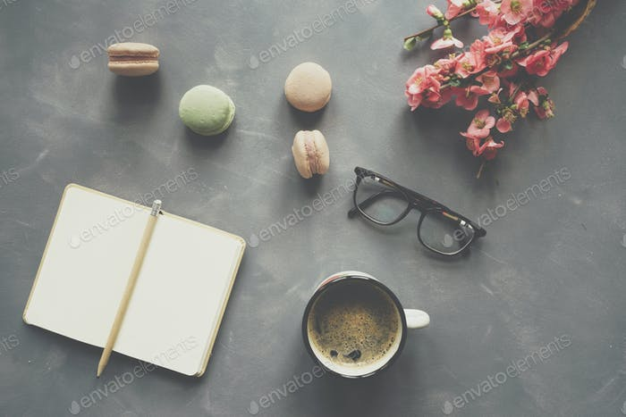 Top view of notebook, coffee, macarons and flowers on cement bac