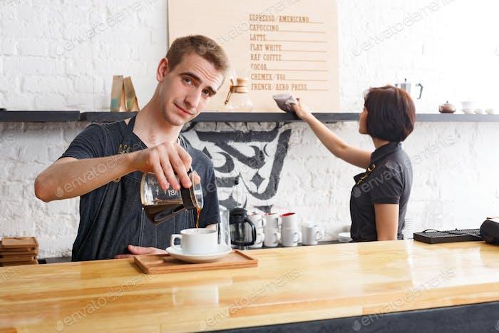Männliche und weibliche Barkeeper brauen frischen Kaffee im Café Interieur