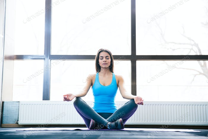 Attractive young woman meditating at gym