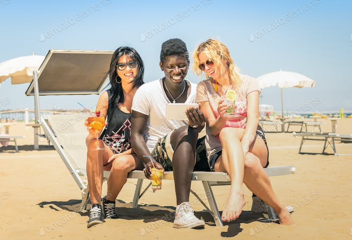 Happy multiracial girl friends drinking cocktails with tablet pc at the beach