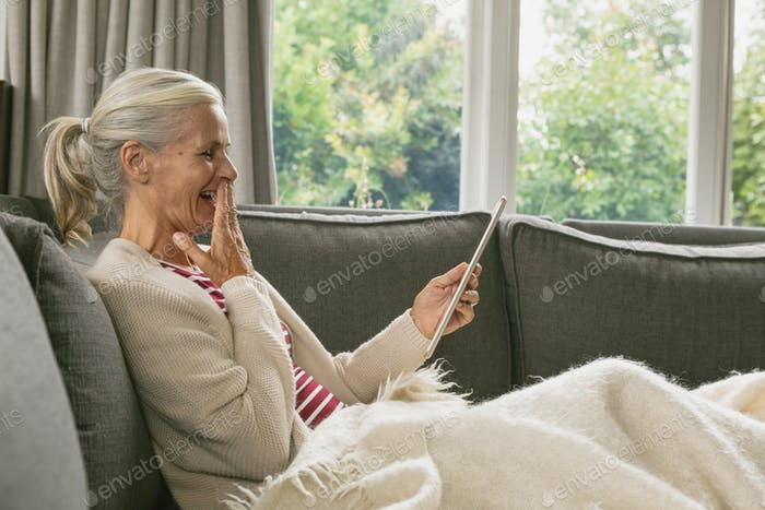 Happy active senior Caucasian woman relaxing on sofa and using digital tablet