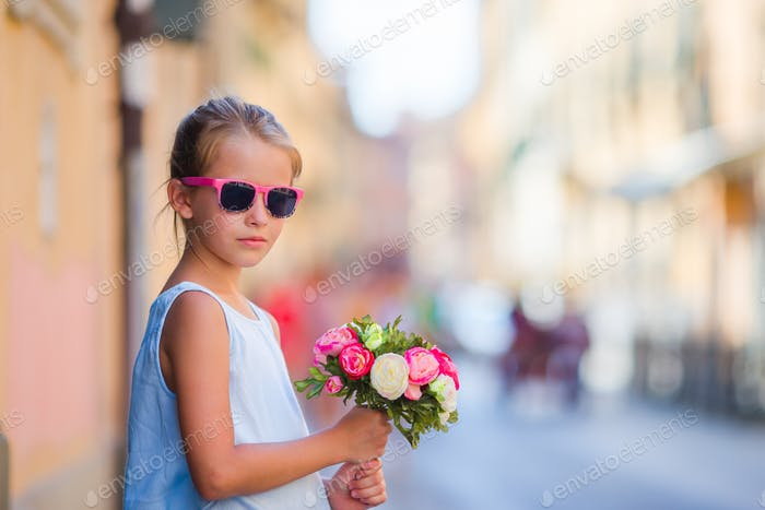 Adorable little girl with flowers bouquet walking in european city