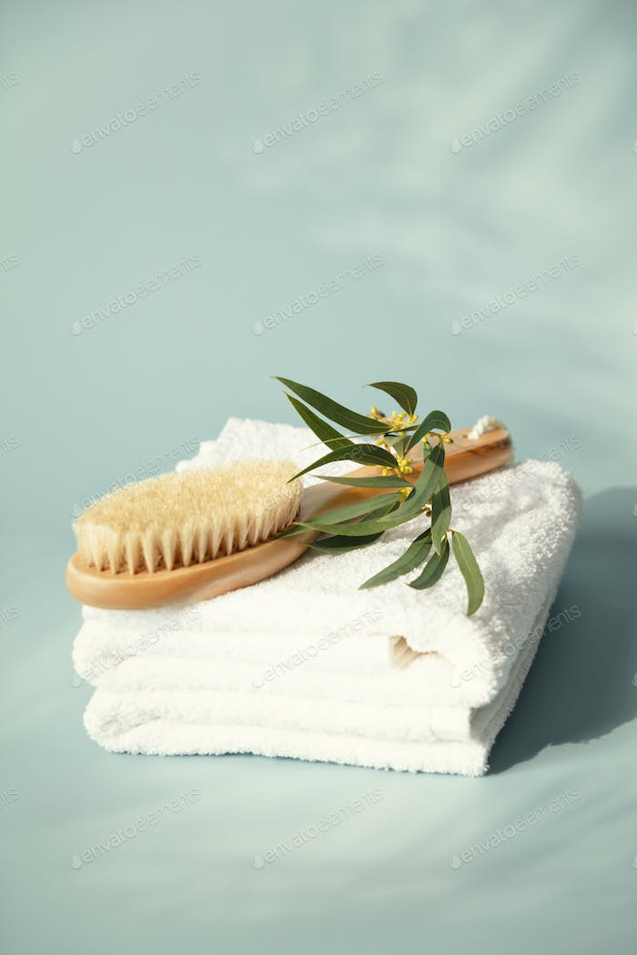 Massage wooden brush on white spa towels with eucalyptus leaves