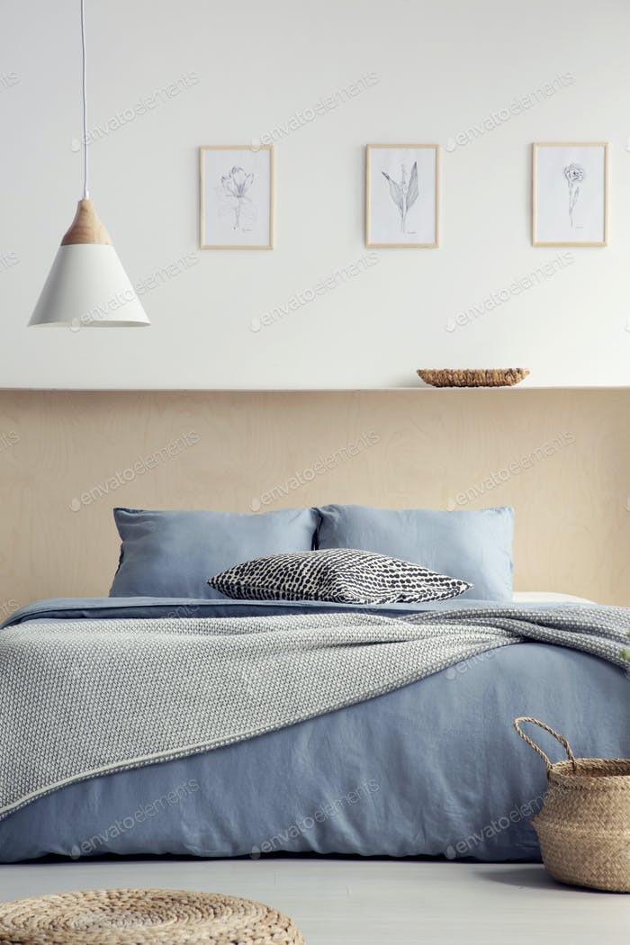 Lamp above blue bed with pillows in boho bedroom interior with p