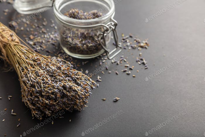 Dried lavender bouquet on black tabletop background and in glass jar.