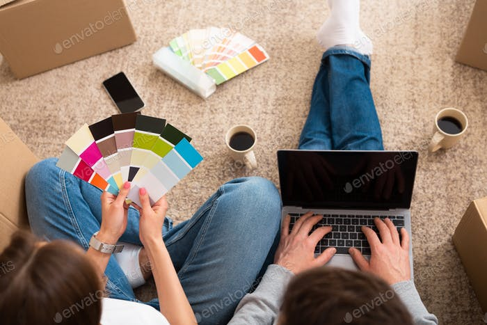 Young couple choosing color palette and furniture at home