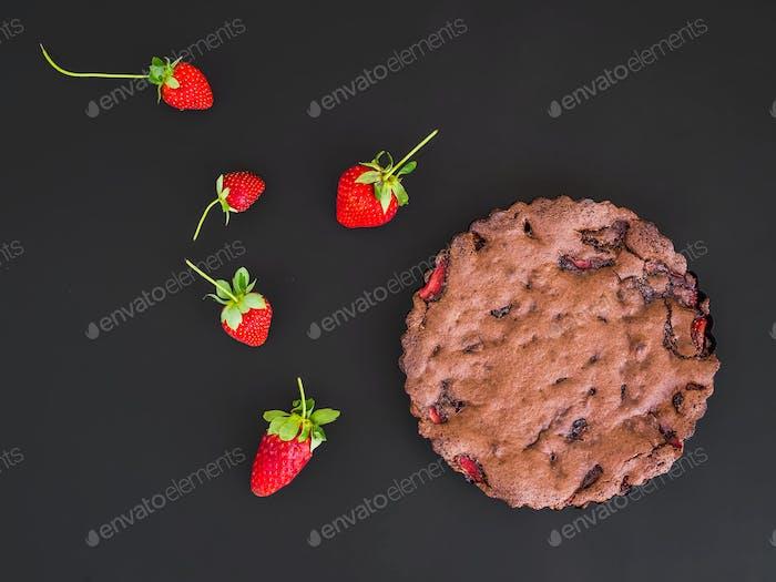 Schokoladen-Erdbeerkuchen mit frischen Erdbeeren auf einer dunklen Brandung