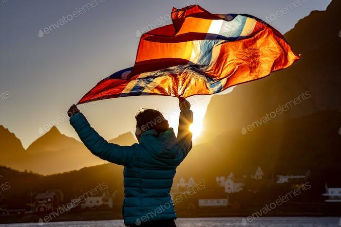 Frau winkt die Flagge von Norwegen bei Sonnenuntergang