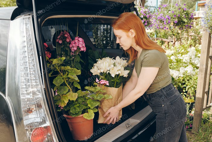 Young flower shop owner packing flowers in car trunk