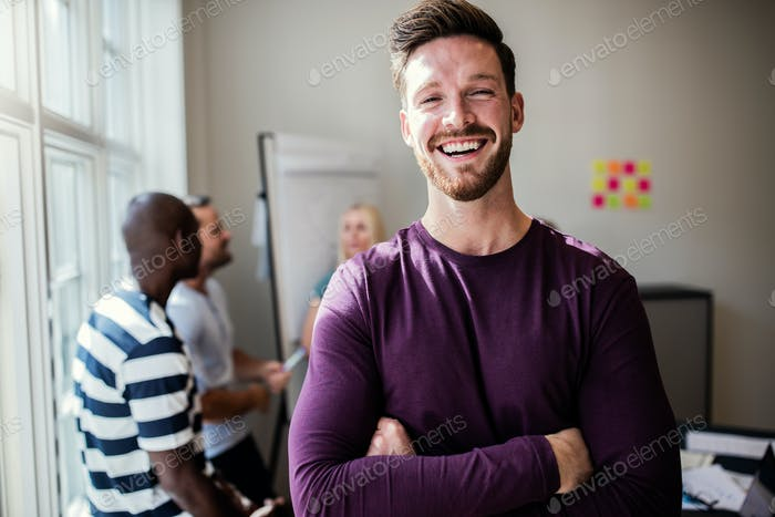 Laughing young designer standing in an office after a presentation