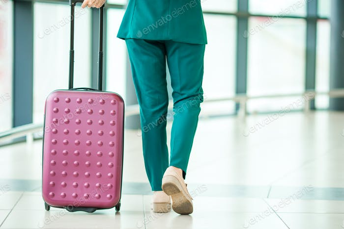 Closeup legs airplane passenger and pink baggage in an airport lounge going for flight aircraft