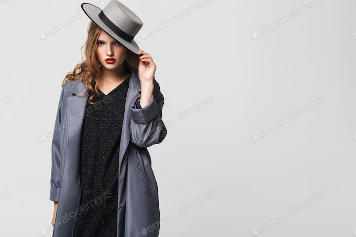 Young beautiful woman with wavy hair in hat and cloak strong looking in camera over gray background