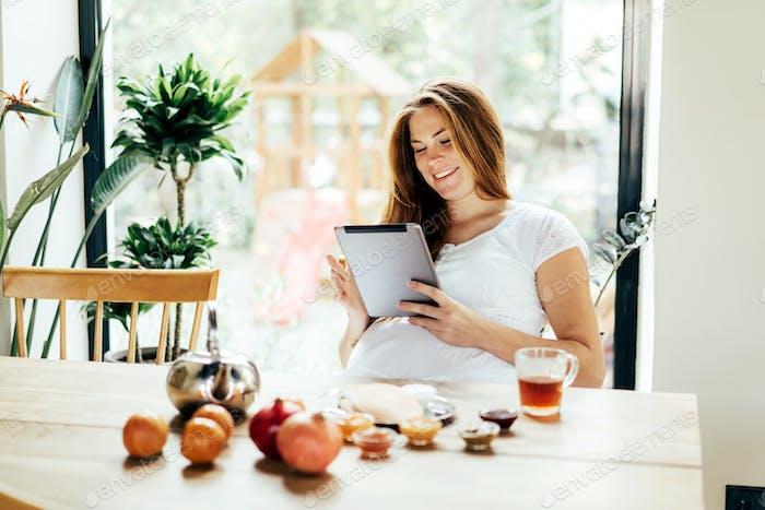 Schwangere Sommersprossen Rothaarige Frau Surfen Computer Gadget Tablet in sozialen Medien.