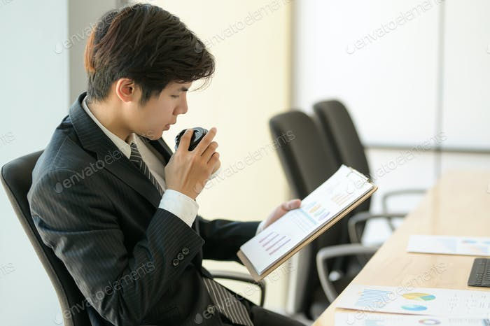 Young executives are checking company earnings. He eats coffee and checks the chart.