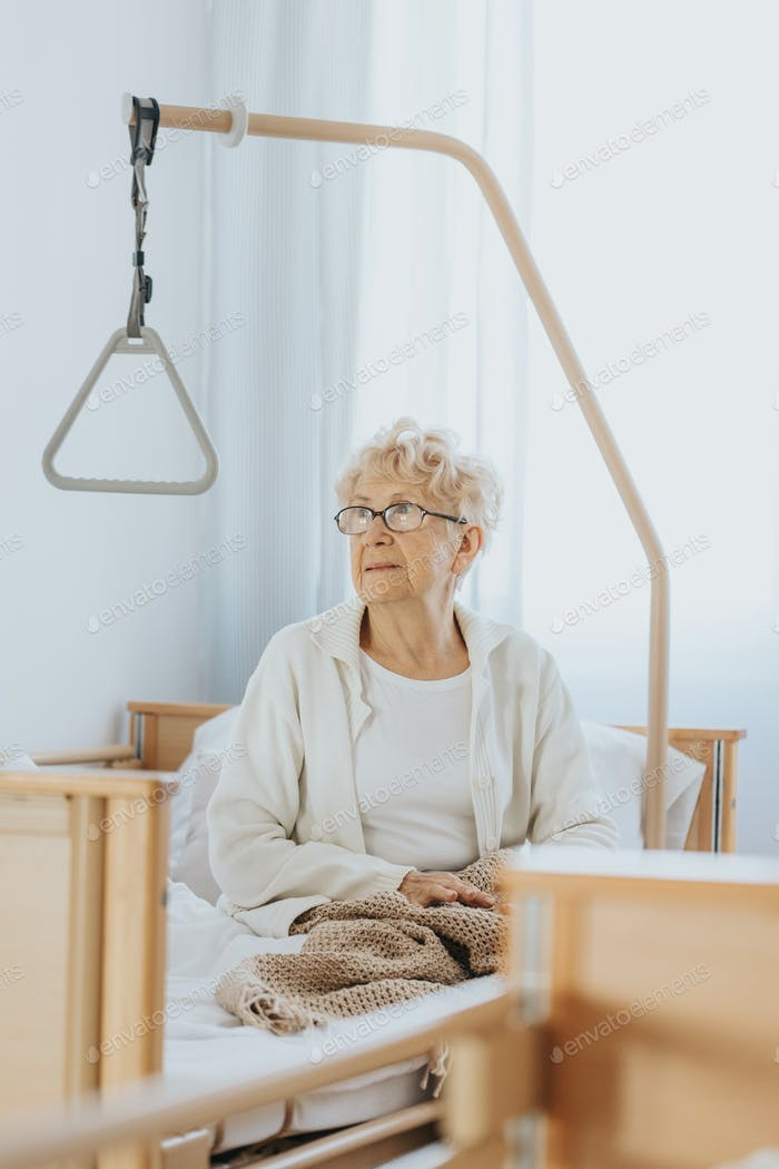 Grandmother with glasses is sitting on the bed in the nursing home