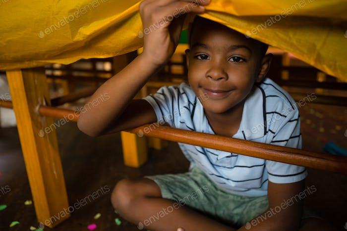 Porträt von niedlichen Jungen sitzen unter Tisch