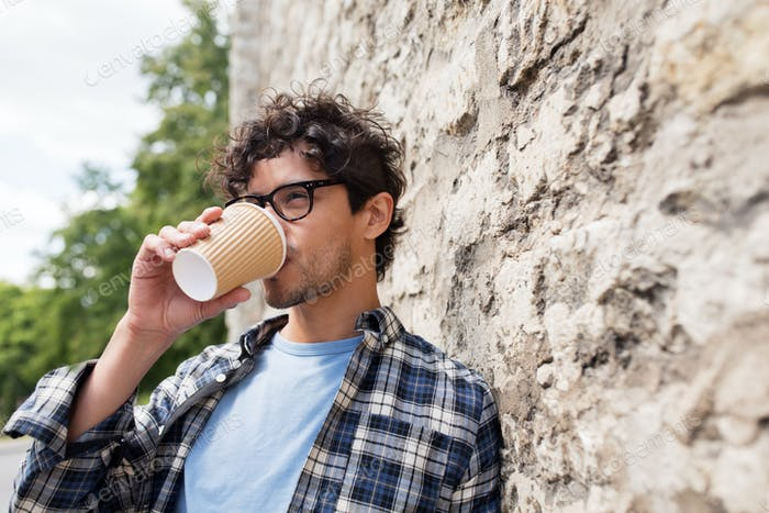 man in eyeglasses drinking coffee over street wall