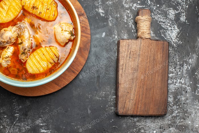 Chicken soup on round cutting board and chopper board