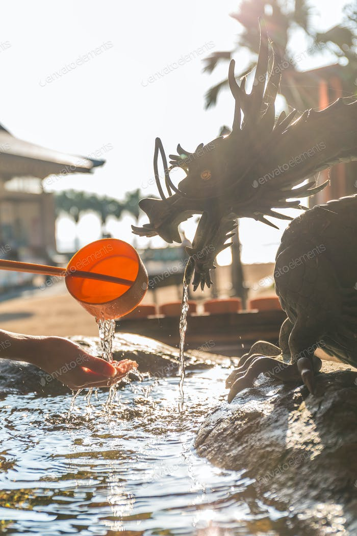 Bamboo water fountain with dragon statue under sunlight