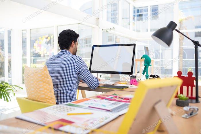 Graphic designer working on computer at desk