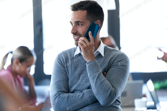 Smiling young businessman talking on mobile phone on coworking space.