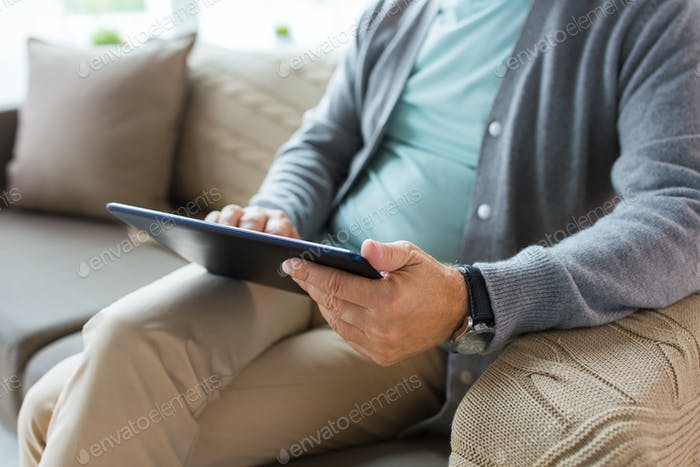close up of senior man with tablet pc on sofa