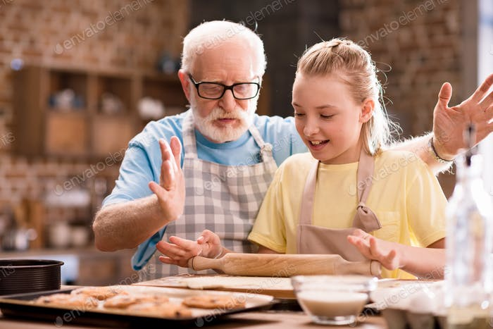 grandfather and granddaughter cooking and kneading dough for cookies with kitchen utensils at